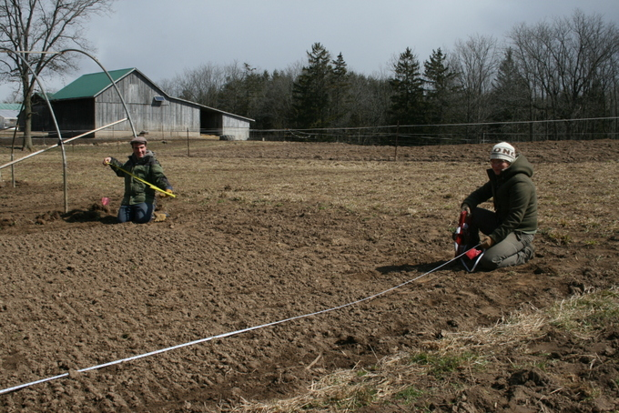 Stephanie and Jean-Francois Langlais Measuring the Area for the Hoop House