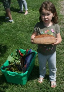 CSA member with First Wood Fired Oven Bread and CSA Basket for the Week!